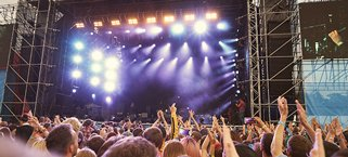 Image of the crowd at a gig in front of the stage.