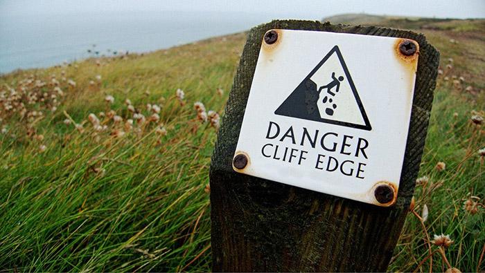 dangerous place sign on cliff