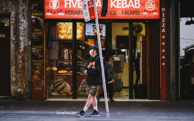 man standing outside shop during coronavirus with mask